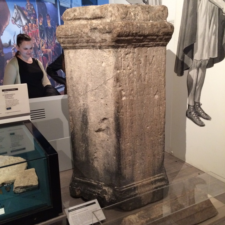 A Roman Pillar.  That;s a picture next to it, not someone hanging.